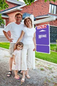 Family in front of newly purchased home