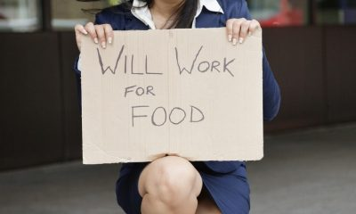 Young Indian businesswoman holding ´Will Work for Food´ sign