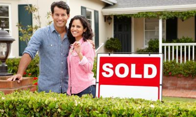 02G69570Hispanic couple outside home with sold sign