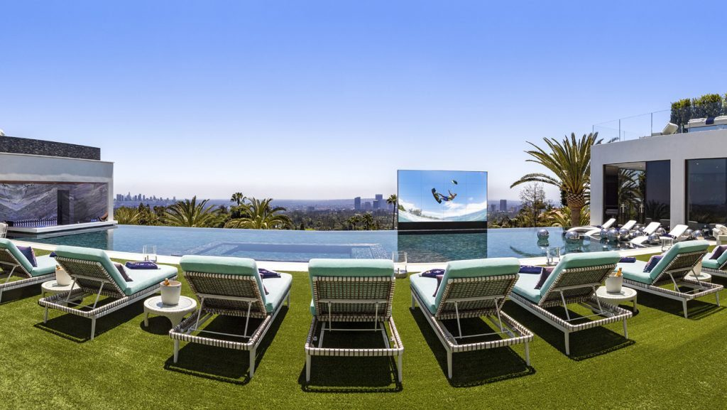 Poolside seating for an 85-foot Italian glass infinity pool and an outdoor hydraulic pop-up theater.